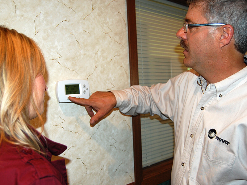 Showing a office worker the use of a new thermostat installed by Viking Mechanical.
